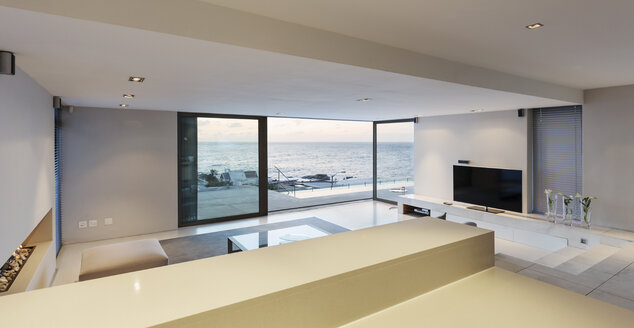 Modern, minimalist luxury living room with patio doors open to ocean view - HOXF01339