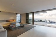 Modern, minimalist luxury living room with gas fireplace and patio doors open to ocean view and patio - HOXF01342