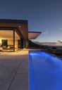 Blue lap swimming pool outside modern luxury home showcase exterior at night - HOXF01354