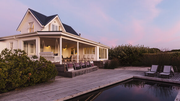 White home showcase exterior beach house at dusk - HOXF01357