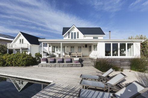 Sunny white home showcase exterior with patio and swimming pool - HOXF01366