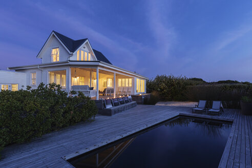 Illuminated white home showcase exterior and swimming pool at night - HOXF01369