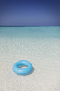Blue inflatable ring floating in tropical ocean - HOXF01378