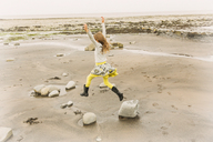 Exuberant girl jumping for joy on beach rocks - HOXF01390