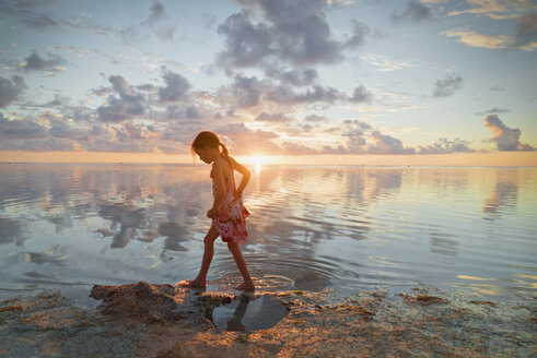 Girl wading in ocean surf on tranquil sunset beach - HOXF01402