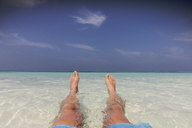 Personal perspective barefoot man relaxing, laying in tropical ocean surf - HOXF01405
