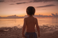 Boy on beach looking at tranquil sunset ocean - HOXF01408