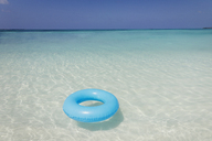 Blue inflatable ring floating in tropical ocean - HOXF01414
