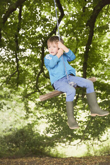 Boy in wellies swinging on tree rope swing - HOXF01417