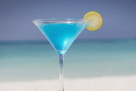 Blue cocktail with lemon slice in martini glass on tropical ocean beach - HOXF01432