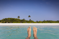 Personal perspective barefoot man floating in tropical ocean with beach view - HOXF01435