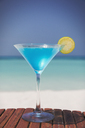 Blue cocktail with lemon slice in martini glass on sunny tropical beach - HOXF01444
