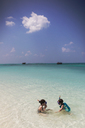 Boy and girl brother and sister snorkeling in sunny blue tropical ocean - HOXF01453