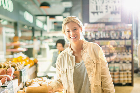 Portrait smiling young woman grocery shopping in market - HOXF01600