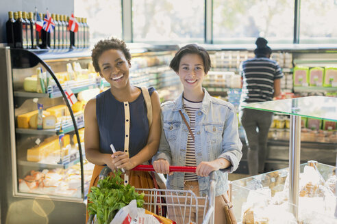 Portrait smiling young lesbian couple, grocery shopping in market - HOXF01603