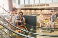 Young lesbian couple using cell phone on escalator in grocery store market - HOXF01609