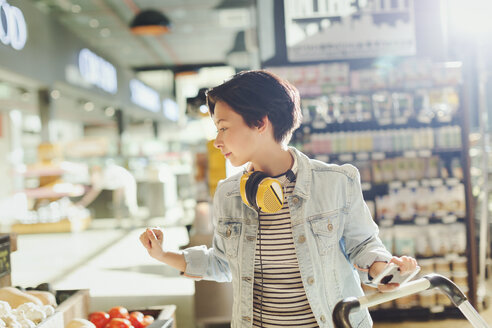 Young woman with headphones browsing, grocery shopping in market - HOXF01618