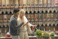 Young couple using cell phone, grocery shopping in market - HOXF01621