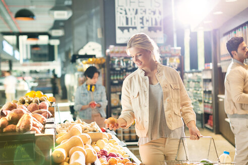 Young woman grocery shopping, browsing produce in market - HOXF01633