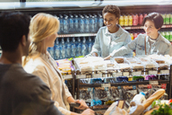 Young friends talking in grocery store market - HOXF01642