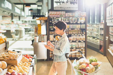 Young woman with headphones using cell phone, grocery shopping in market - HOXF01663