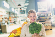 Portrait smiling young woman holding bunch of kale in grocery store market - HOXF01666