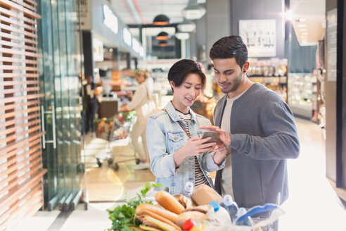 Young couple using cell phone in grocery store market - HOXF01669