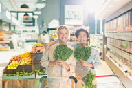 Portrait smiling young female friends holding kale in grocery store market - HOXF01672