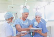 Surgeons and nurse using clipboard and digital tablet in operating room - HOXF01687