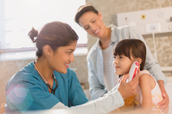 Female nurse using digital thermometer in ear of girl patient in examination room - HOXF01690