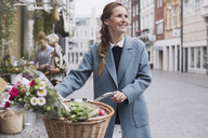 Smiling woman walking bicycle with flowers in basket on city street - HOXF01783