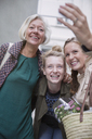 Smiling mother and daughters taking selfie with camera phone - HOXF01801