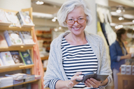 Portrait smiling mature female shopper using cell phone in shop - HOXF01846