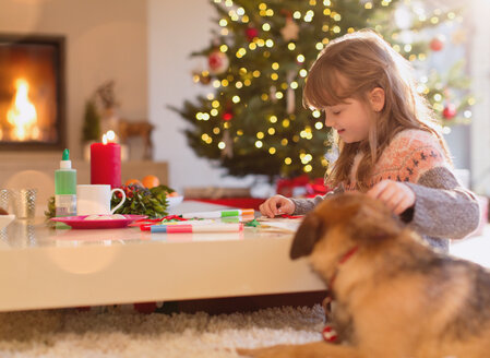 Dog watching girl coloring with markers in Christmas living room - HOXF01879