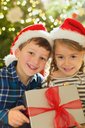 Portrait smiling brother and sister in Santa hats holding Christmas gift - HOXF01882