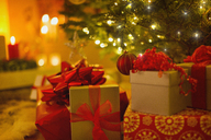 Christmas gifts with red bows under illuminated Christmas tree - HOXF01888