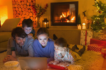 Family eating popcorn and watching video on laptop in ambient Christmas living room with fireplace - HOXF01891