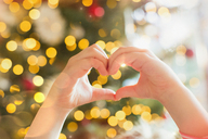 Close up hands of girl forming heart-shape in front of Christmas tree - HOXF01921