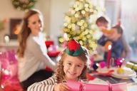 Portrait smiling girl holding Christmas cracker at dinner table - HOXF01924