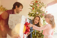 Parents giving large Christmas gift to daughter near Christmas tree - HOXF01939