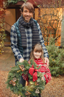 Portrait smiling father and daughter with Christmas wreath - HOXF01945