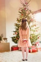 Girl in pink dress holding Christmas gift in front of Christmas tree - HOXF01954