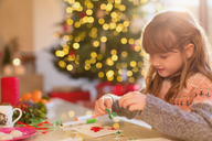 Girl making Christmas decorations at table - HOXF01966