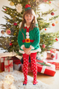Portrait smiling girl wearing elf costume in front of Christmas tree - HOXF01978