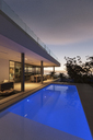 Tranquil blue lap swimming pool outside modern luxury home showcase exterior - HOXF01984