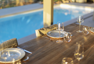 Placesettings on wood patio table at poolside - HOXF01996
