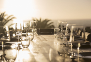 Glasses on sunny sunset patio table - HOXF02002