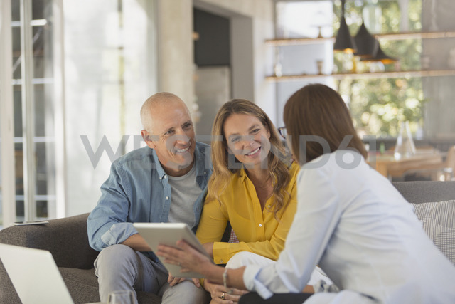 Financial advisor with digital tablet meeting with couple in living room - HOXF02014
