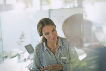 Serious female doctor with digital tablet talking to male patient in doctor's office - HOXF02017