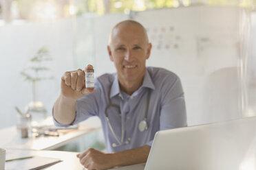 Portrait smiling male doctor holding prescription bottle in doctor's office - HOXF02020